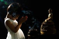 Asiatisches kleines chinesisches Mädchen, das vor Buddha betet Lizenzfreie Stockbilder