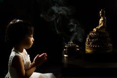 Asiatisches kleines chinesisches Mädchen, das vor Buddha betet Stockfotos