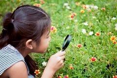 Asiatisches kleines Kindermädchen, das durch eine Lupe schaut Lizenzfreie Stockbilder