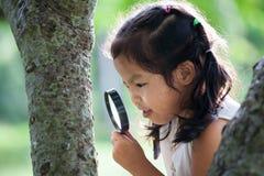 Asiatisches kleines Kindermädchen, das durch eine Lupe schaut Stockbild