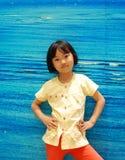 Asiatisches kleines Mädchen auf blauem Hintergrund Lizenzfreie Stockbilder