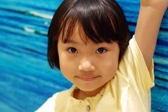 Asiatisches kleines Mädchen auf blauem Hintergrund Stockbilder