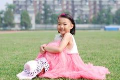 Asiatisches kleines Mädchen, das auf dem Gras sitzt Stockbilder