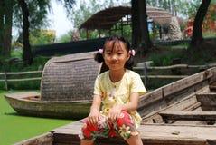 Asiatisches kleines Mädchen, das auf einem hölzernen Boot sitzt Lizenzfreie Stockbilder