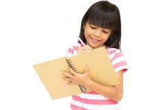 Asiatisches kleines Mädchen, das ein Notizbuch schreibt Lizenzfreies Stockbild