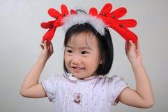 Asiatisches kleines Mädchen, das ein Renstirnband trägt Stockbild
