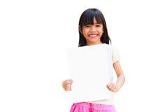 Asiatisches kleines Mädchen, das ein weißes Blatt Papier hält Stockfoto