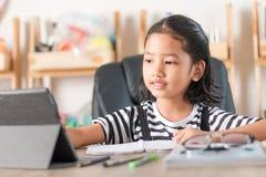 Asiatisches kleines Mädchen, das Hausarbeit auf dem ausgewählten Fokus des Holztischs SH tut stockbild