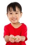 Asiatisches kleines Mädchen, das Münzen für die Rettung hält Lizenzfreie Stockbilder