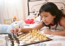 Asiatisches kleines Mädchen, das Schach mit Teddybärkaninchen spielt Lizenzfreies Stockfoto