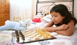 Asiatisches kleines Mädchen, das Schach mit Teddybärkaninchen spielt Stockbilder