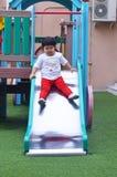 Asiatisches kleines Mädchen, das Schieber am Spielplatz Thailand spielt Lizenzfreie Stockfotos
