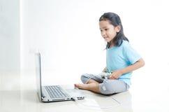 Asiatisches kleines Mädchen, das Spiele mit Laptop-Computer spielen und joystic Lizenzfreie Stockfotografie