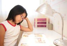 Asiatisches kleines Mädchen, das zu Hause studiert Stockfoto