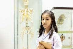 Asiatisches kleines Mädchen in Doktorkostüm mit dem Skelett in Klassenzimmer a lizenzfreie stockfotografie