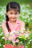 Asiatisches kleines Mädchen mit Blume Stockbild
