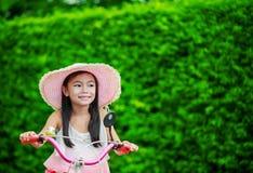 Asiatisches kleines Mädchen mit ihrem Fahrrad Stockfoto