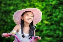 Asiatisches kleines Mädchen mit ihrem Fahrrad Lizenzfreies Stockbild