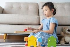 Asiatisches kleines Mädchen spielt Spielzeug im Wohnzimmer Kleinkind nett für Freiheitstätigkeit stockbilder