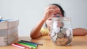 Asiatisches kleines Mädchen, welches die Münze in ein Klarglasglas mit dem Buch auf Tabellenmetapher-Einsparungsgeld für Bildungs stock video