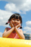 Asiatisches kleines Mädchen auf dem blauen Himmel Stockfoto