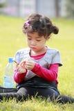 Asiatisches kleines Mädchen, das auf Gras spielt Stockfoto