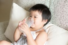 Asiatisches kleines nettes Mädchen ist, trinkend halten und ein Glas Milch I stockfoto