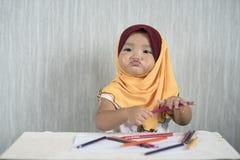 Asiatisches Kleinkind/Baby tragendes hijab hat den Spaß, der lernt, Bleistifte bei der Herstellung des lustigen Gesichtes zu benu Stockfoto