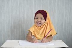 Asiatisches Kleinkind/Baby tragendes hijab hat den Spaß, der lernt, Bleistifte beim Betrachten des leeren Raumes zu benutzen Stockbild