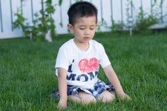 Asiatisches Kleinkind, das auf dem grünen Gras spielt stockfotos