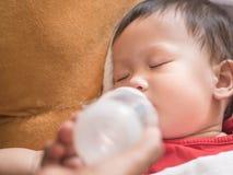 Asiatisches Kleinkind, das Flasche Milch beim Schlafen isst Stockfotografie