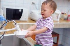 Asiatisches Kleinkindbabykind, das den Spaß tut die Teller/wäscht Teller in der Küche steht und hat Stockfotos