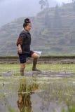 Asiatisches Landwirtmädchen geht barfuß durch Schlamm von Reisfeldern Stockfotos