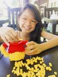 Asiatisches langes Mädchen des schwarzen Haares trägt orange Brillen Sie ist stockfotos