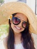 Asiatisches langes Mädchen des schwarzen Haares trägt schwarze Sonnenbrille, Stroh ha stockfotografie