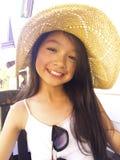 Asiatisches langes Mädchen des schwarzen Haares trägt Strohhut Sie sitzt stockbild