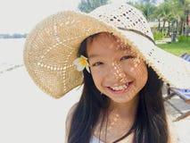 Asiatisches langes Mädchen des schwarzen Haares trägt Strohhut und weiße Blume lizenzfreie stockfotos