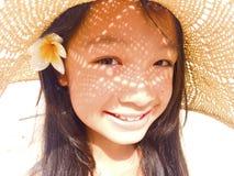 Asiatisches langes Mädchen des schwarzen Haares trägt Strohhut und weiße Blume stockfotografie