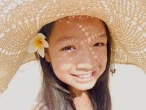 Asiatisches langes Mädchen des schwarzen Haares trägt Strohhut und weiße Blume lizenzfreie stockbilder