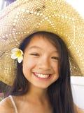 Asiatisches langes Mädchen des schwarzen Haares trägt Strohhut und weiße Blume lizenzfreie stockfotografie