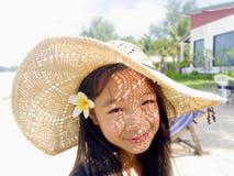 Asiatisches langes Mädchen des schwarzen Haares trägt Strohhut und weißes flowe lizenzfreie stockbilder