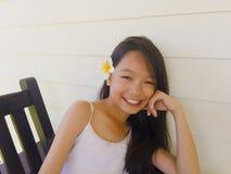Asiatisches langes Mädchen des schwarzen Haares trägt weiße Blume hinter dem ri lizenzfreies stockbild