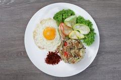 Asiatisches Lebensmittel, gebratener Reis in einer weißen Platte auf einem hölzernen Hintergrund Lizenzfreie Stockfotos