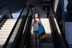 Asiatisches Mädchen auf einer Rolltreppe stockfoto