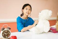 Asiatisches Mädchen, das als Doktor mit Herzkrankheit gespielt wird lizenzfreies stockfoto