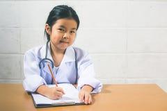 Asiatisches Mädchen, das als Doktorschreiben Verordnung und preparin trägt Lizenzfreies Stockbild