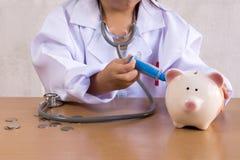 Asiatisches Mädchen, das als Doktorsorgfalt Sparschwein spielt Stockfotografie