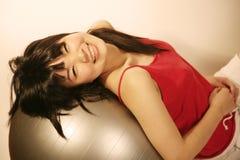 Asiatisches Mädchen, das auf Übungskugel sich lehnt Stockfotos