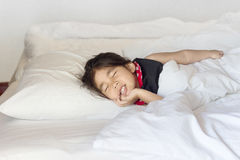 Asiatisches Mädchen, das auf Bett schläft stockbilder