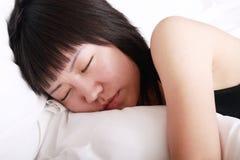 Asiatisches Mädchen, das auf Bett schläft Lizenzfreie Stockbilder